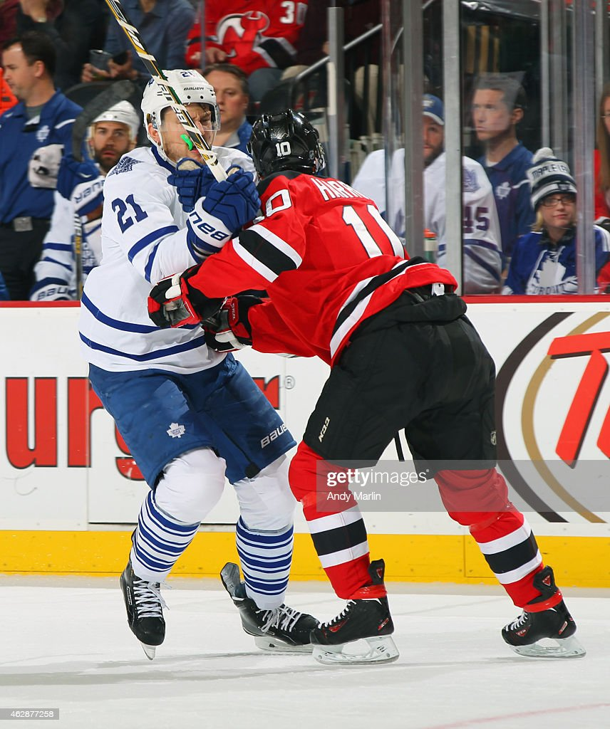 James van Riemsdyk of the Toronto Maple Leafs is checked by Peter Harrold of the New Jersey Devils during the game at the Prudential Center on...