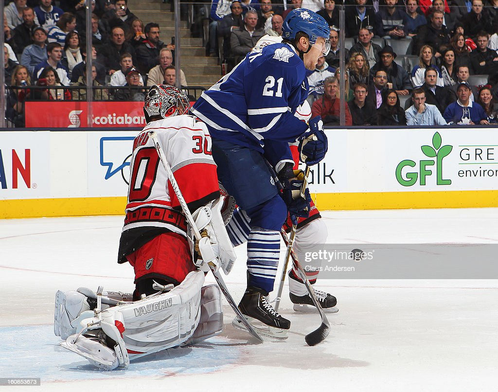 James van Riemsdyk #21 of the Toronto Maple Leafs is hit by the puck in front of Cam Ward #30 of the Carolina Hurricanes in a game on February 4, 2013 at the Air Canada Centre in Toronto, Canada. The Hurricanes defeated the Leafs 4-1.