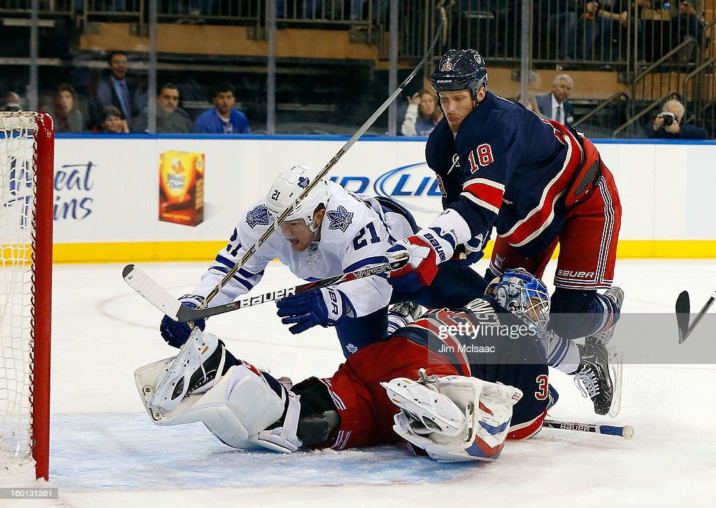 James van Riemsdyk #21 of the Toronto Maple Leafs is knocked over <a gi-track='captionPersonalityLinkClicked' href=/galleries/search?phrase=Henrik+Lundqvist&family=editorial&specificpeople=217958 ng-click='$event.stopPropagation()'>Henrik Lundqvist</a> #30 of the New York Rangers by <a gi-track='captionPersonalityLinkClicked' href=/galleries/search?phrase=Marc+Staal&family=editorial&specificpeople=3809026 ng-click='$event.stopPropagation()'>Marc Staal</a> #18 after scoring a first period goal at Madison Square Garden on January 26, 2013 in New York City.