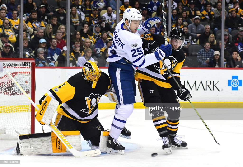 James van Riemsdyk #25 of the Toronto Maple Leafs is pushed by Brian Dumoulin #8 of the Pittsburgh Penguins at PPG PAINTS Arena on December 9, 2017 in Pittsburgh, Pennsylvania.