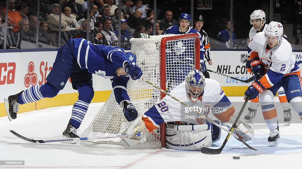 James van Riemsdyk #21 of the Toronto Maple Leafs is topped on a wraparound by goalie <a gi-track='captionPersonalityLinkClicked' href=/galleries/search?phrase=Evgeni+Nabokov&family=editorial&specificpeople=171380 ng-click='$event.stopPropagation()'>Evgeni Nabokov</a> #20 and <a gi-track='captionPersonalityLinkClicked' href=/galleries/search?phrase=Mark+Streit&family=editorial&specificpeople=636976 ng-click='$event.stopPropagation()'>Mark Streit</a> #2 of the New York Islanders during NHL game action January 24, 2013 at the Air Canada Centre in Toronto, Ontario, Canada.