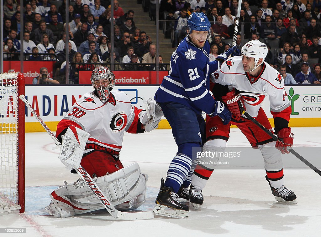 James van Riemsdyk #21 of the Toronto Maple Leafs looks to tip a shot between Cam Ward #30 and Jay Harrison #44 of the Carolina Hurricanes in a game on February 4, 2013 at the Air Canada Centre in Toronto, Canada. The Hurricanes defeated the Leafs 4-1.