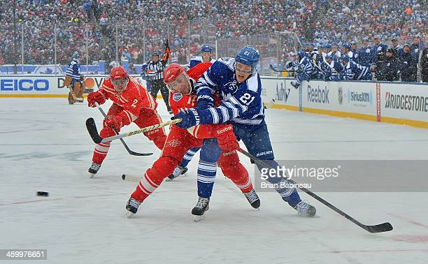 James van Riemsdyk of the Toronto Maple Leafs shoots the puck as Pavel Datsyuk of the Detroit Red Wings tries to defend the play in the first period...