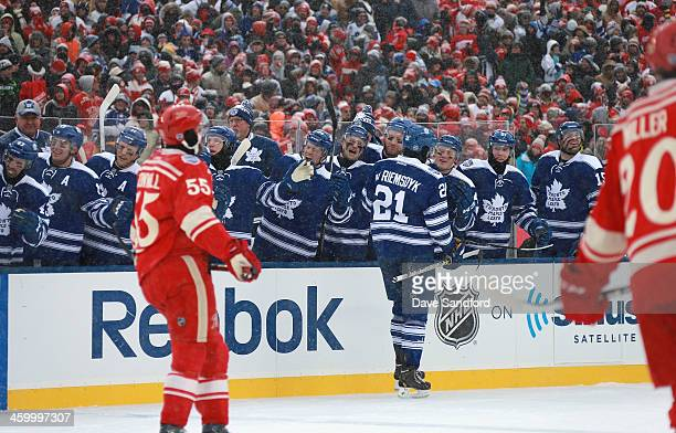 James van Riemsdyk of the Toronto Maple Leafs skates by the Leafs bench to celebrate his goal with teammates as Niklas Kronwall and Drew Miller of...