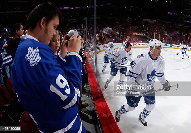 James van Riemsdyk of the Toronto Maple Leafs skates past a fan taking a photo during warm ups to the NHL game against the Arizona Coyotes at Gila...