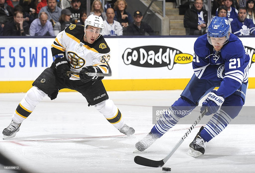 James van Riemsdyk #21 of the Toronto Maple Leafs skates the puck away from Brad Marchand #63 of the Boston Bruins during NHL game action February 2, 2013 at the Air Canada Centre in Toronto, Ontario, Canada.