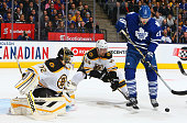 James van Riemsdyk of the Toronto Maple Leafs tips the puck against Niklas Svedberg and Dennis Seidenberg of the Boston Bruins during NHL game action...