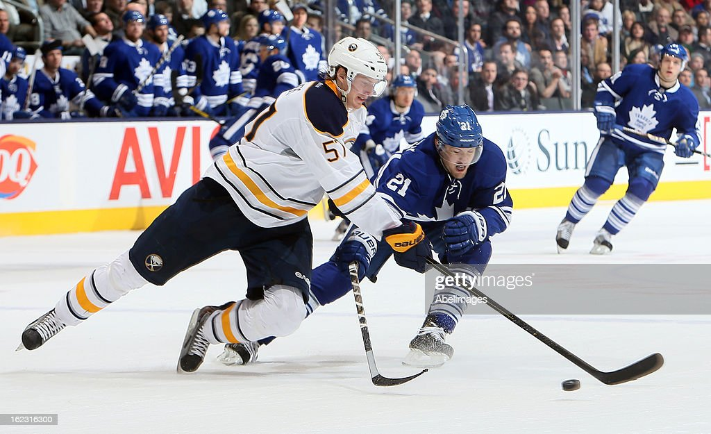 James van Riemsdyk #21 of the Toronto Maple Leafs trips up <a gi-track='captionPersonalityLinkClicked' href=/galleries/search?phrase=Tyler+Myers&family=editorial&specificpeople=4595080 ng-click='$event.stopPropagation()'>Tyler Myers</a> #57 of the Buffalo Sabres during NHL action at the Air Canada Centre February 21, 2013 in Toronto, Ontario, Canada.