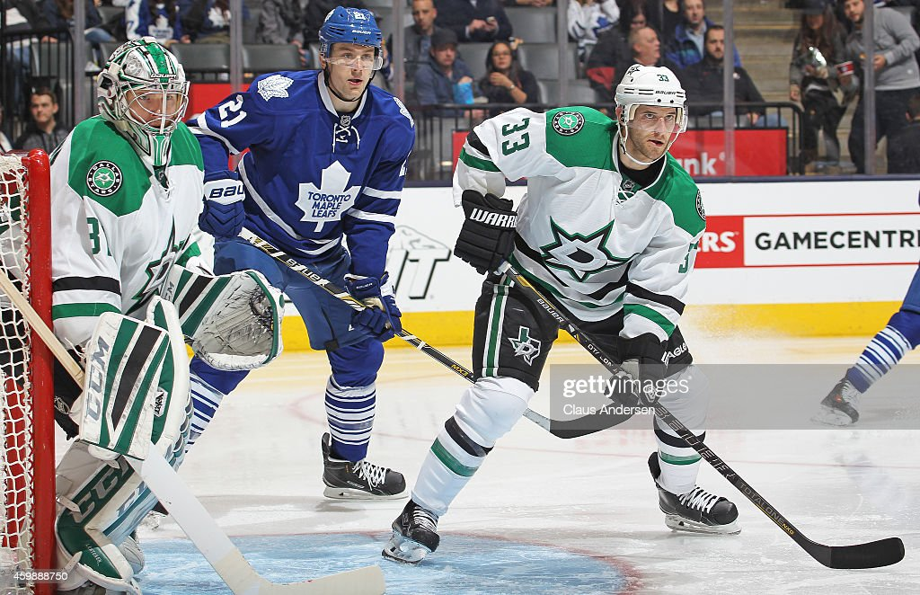 James van Riemsdyk of the Toronto Maple Leafs waits for a pass between Kari Lehtonen and Alex Goligoski of the Dallas Stars during an NHL game at the...