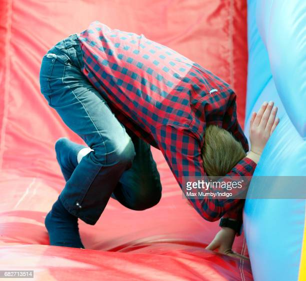 James Viscount Severn plays on an inflatable slide as he accompanied by his parents The Earl and Countess of Wessex attends day 4 of the Royal...