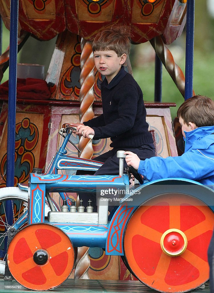 James, Viscount Severn (C), son of Prince Edward, Earl of Wessex and Sophie, Countess of Wessex, rides on the fun fair carousel on day 4 of the Royal Windsor Horse Show on May 11, 2013 in Windsor, England.