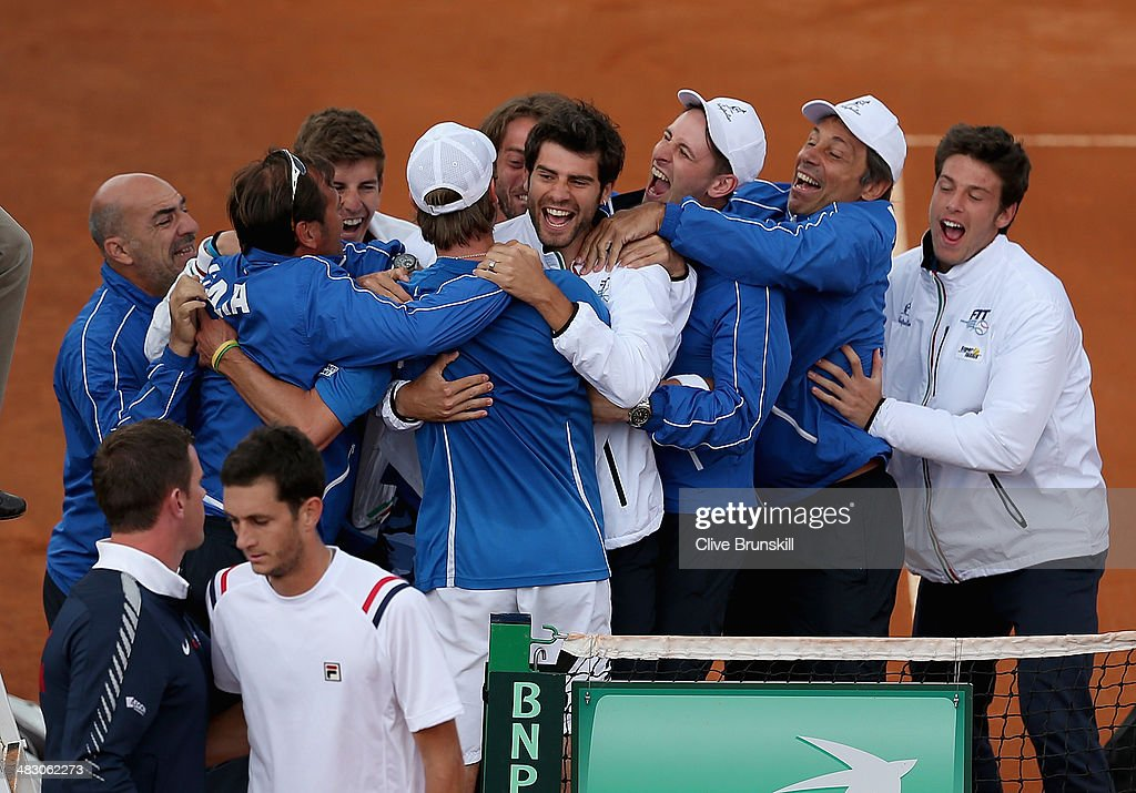 James Ward of Great Britain is consoled by his team captain <a gi-track='captionPersonalityLinkClicked' href=/galleries/search?phrase=Leon+Smith+-+Tennis+Coach&family=editorial&specificpeople=12698515 ng-click='$event.stopPropagation()'>Leon Smith</a> watched by a jubilant Italian team after losing the fifth and decisive rubber to Andreas Seppi of Italy during day three of the Davis Cup World Group Quarter Final match between Italy and Great Britain at Tennis Club Napoli on April 6, 2014 in Naples, Italy.