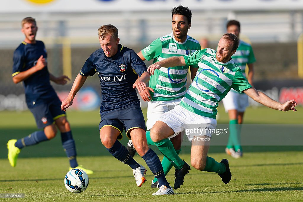 James Ward-Prowse of Southampton avoids the tackle of David Vandecauter of KSK Hasselt during the pre-season friendly match between KSK Hasselt and Southampton at the Stedelijk Sportstadion on July 17, 2014 in Hasselt, Belgium.