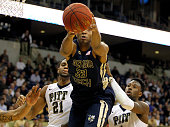 James White of the Georgia Tech Yellow Jackets pulls down a rebound against Sheldon Jeter and Jamel Artis of the Pittsburgh Panthers during the game...