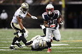 James White of the New England Patriots breaks a tackle by Henry Coley of the New Orleans Saints during the third quarter of a preseason game at the...
