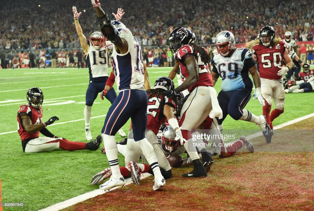 TOPSHOT - James White #28 of the New England Patriots scores the game winning touchdown in overtime against the Atlanta Falcons during Super Bowl 51 at NRG Stadium on February 5, 2017 in Houston, Texas / AFP PHOTO / Timothy A. CLARY