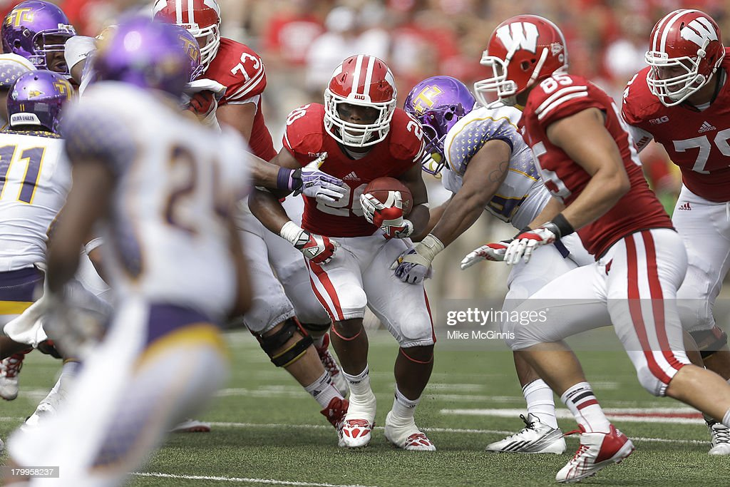 James White #20 of the Wisconsin Badgers runs throw a hole in the defensive line of the Tennessee Tech Golden Eagles during the game at Camp Randall Stadium on September 07, 2013 in Madison, Wisconsin.