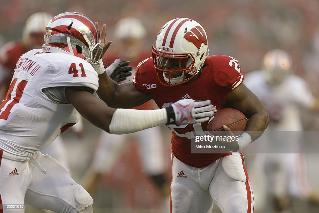 James White #20 of the Wisconsin Badgers runs with the football before getting tackled by Clyde Newton #41 of the Indiana Hoosiers during the first half of play at Camp Randall Stadium on November 16, 2013 in Madison, Wisconsin.
