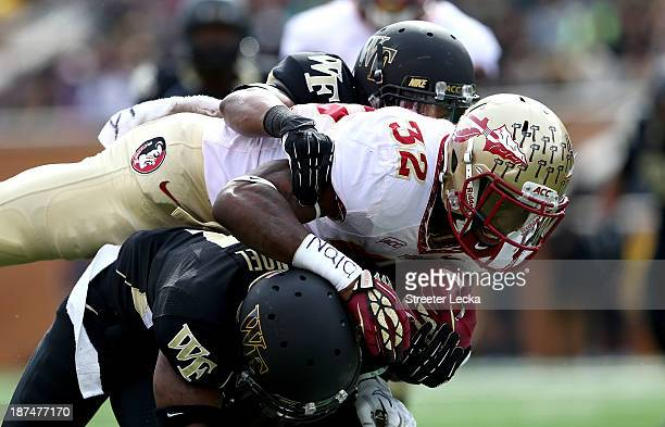 James Wilder Jr #32 of the Florida State Seminoles tries to get away from teammates Merrill Noel and Anthony Wooding Jr #11 of the Wake Forest Demon...