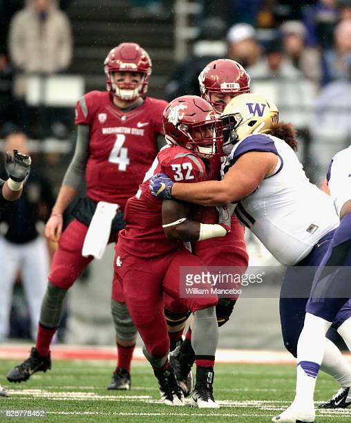 James Williams of the Washington State Cougars carries the ball against Elijah Qualls of the Washington Huskies in the first half of the 109th Apple...