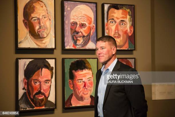 James Williamson US Air Force Chief Warrant Officer Three stands in front of a painting of him painted by former US President George W Bush for the...