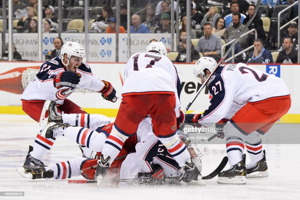 James Wisniewski #21, Brandon Dubinsky #17, Ryan Murray #27 and Cam Atkinson #13, all of the Columbus Blue Jackets, celebrate with Matt Calvert #11 who scored the game-winning goal in the second overtime against the Pittsburgh Penguins in Game Two of the First Round of the 2014 NHL Stanley Cup Playoffs on April 19, 2014 at CONSOL Energy Center in Pittsburgh, Pennsylvania. Columbus defeated Pittsburgh 4-3 for their franchise first playoff win.