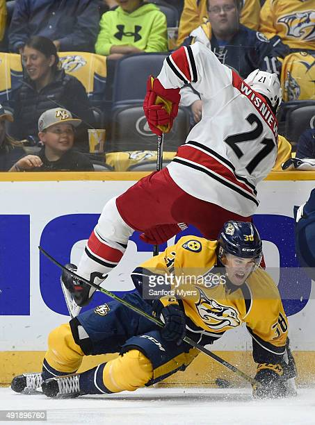 James Wisniewski of the Carolina Hurricanes gets pinched into the boards as Viktor Arvidsson of the Nashville Predators slides into him during the...