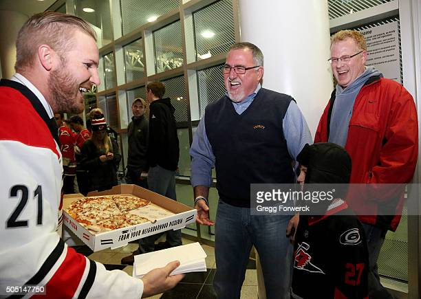 James Wisniewski of the Carolina Hurricanes hands out pizza to those standing in line for Canes College and Military Rush tickets prior to an NHL...