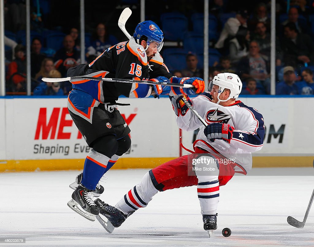 James Wisniewski of the Columbus Blue Jackets is checked by Cal Clutterbuck of the New York Islanders at Nassau Veterans Memorial Coliseum on March...