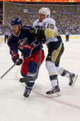 James Wisniewski of the Columbus Blue Jackets is checked by Tanner Glass of the Pittsburgh Penguins during Game Six of the First Round of the 2014...