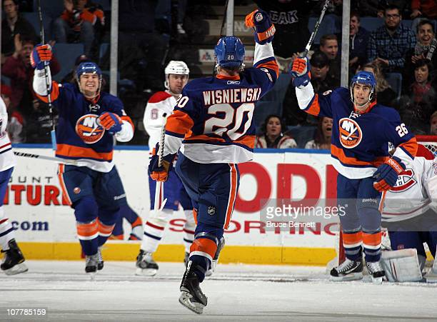 James Wisniewski of the New York Islanders celebrates his power play goal at 422 of the third period along with PA Parenteau and Matt Moulson against...