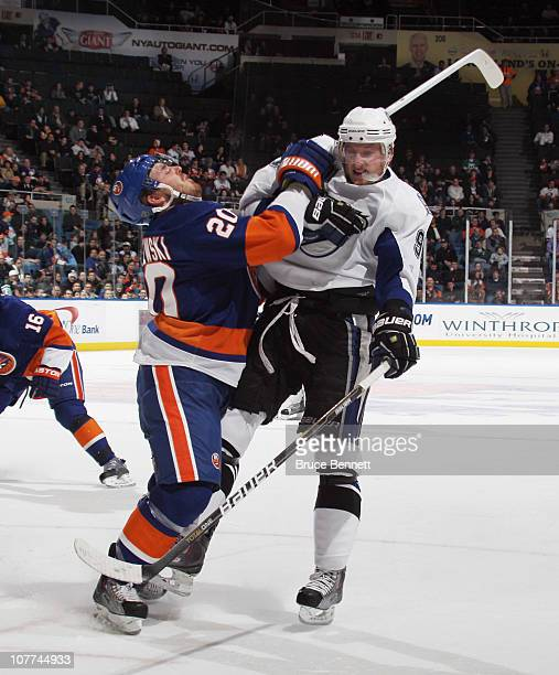 James Wisniewski of the New York Islanders hits Steven Stamkos of the Tampa Bay Lightning at the Nassau Coliseum on December 22 2010 in Uniondale New...