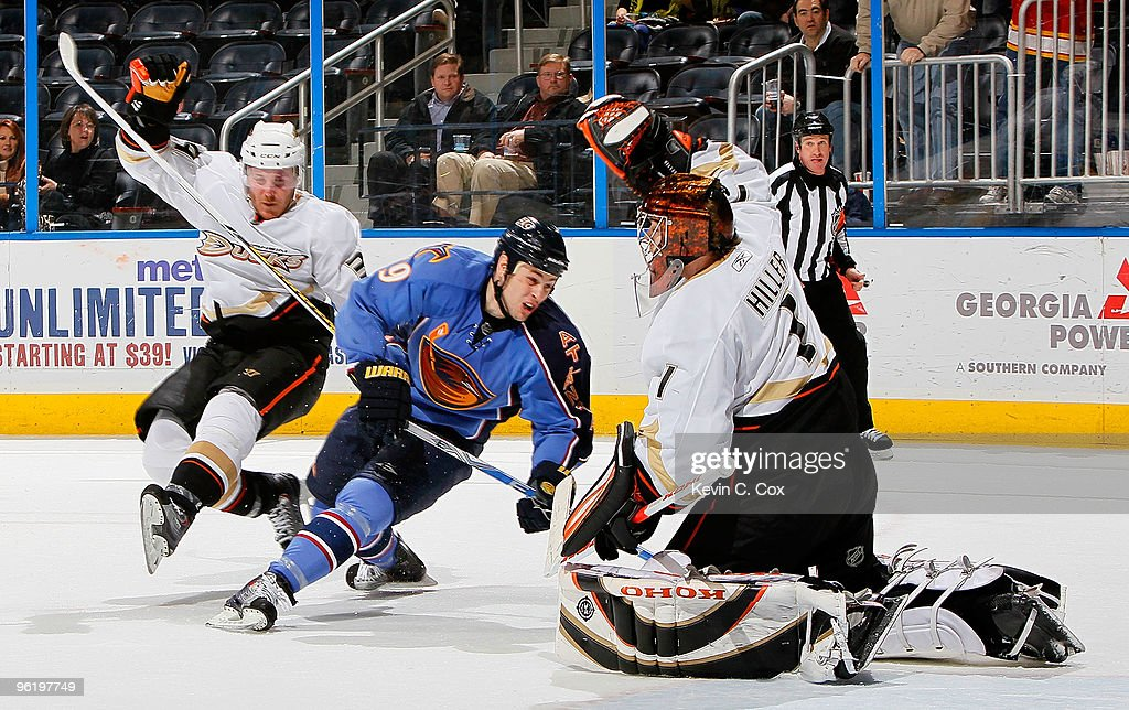 James Wisniewski slips up as goaltender Jonas Hiller of the Anaheim Ducks defends a shot on goal by Marty Reasoner of the Atlanta Thrashers at...