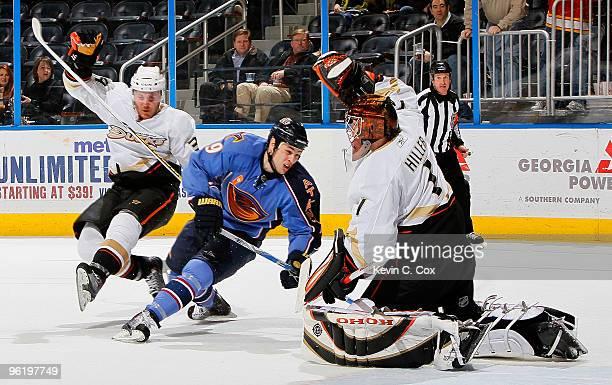 James Wisniewski slips up as goaltender Jonas Hiller of the Anaheim Ducks defends a shot on goal by Marty Reasoner of the Atlanta Thrashers at...