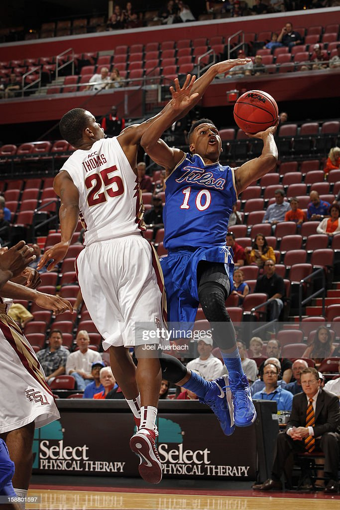 James Woodard #10 of the Tulsa Golden Hurricane goes to the basket against Aaron Thomas #25 of the Florida State Seminoles at the MetroPCS Orange Bowl Basketball Classic on December 29, 2012 at the BB&T Center in Sunrise, Florida. The Seminoles defeated the Golden Hurricane 82-63.