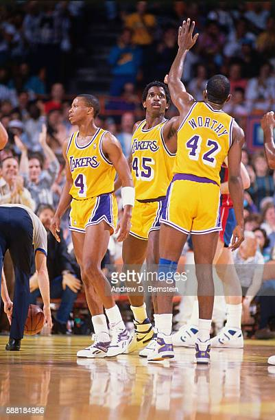 James Worthy and AC Green of the Los Angeles Lakers high five during a game against the Detroit Pistons circa 1988 at The Forum in Los Angeles...