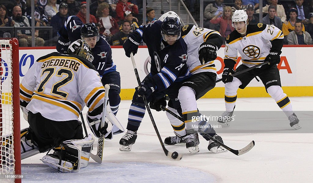 James Wright #17 and Jim Slater #19 of the Winnipeg Jets battle for the puck with Matt Bartkowski #43 of the Boston Bruins in front of the Boston net in second period action during an NHL preseason game at the MTS Centre on September 26, 2013 in Winnipeg, Manitoba, Canada.