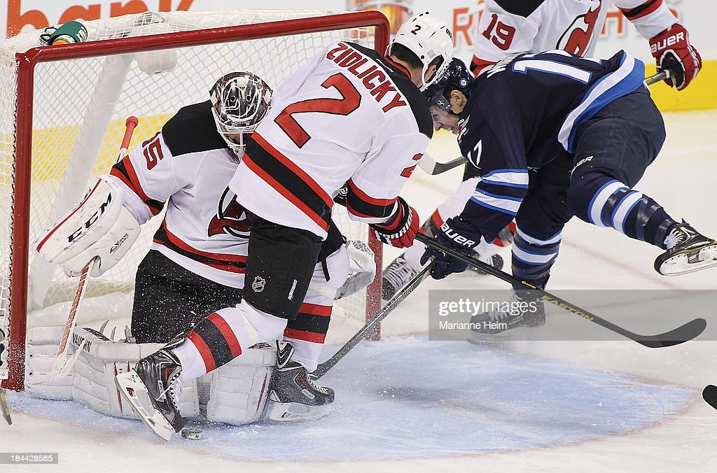 James Wright #17 of the Winnipeg Jets battles with <a gi-track='captionPersonalityLinkClicked' href=/galleries/search?phrase=Marek+Zidlicky&family=editorial&specificpeople=203291 ng-click='$event.stopPropagation()'>Marek Zidlicky</a> #2 of the New Jersey Devils in front of goaltender <a gi-track='captionPersonalityLinkClicked' href=/galleries/search?phrase=Cory+Schneider&family=editorial&specificpeople=696908 ng-click='$event.stopPropagation()'>Cory Schneider</a> #35 in third period action of an NHL game at the MTS Centre on October 13, 2013 in Winnipeg, Manitoba, Canada.