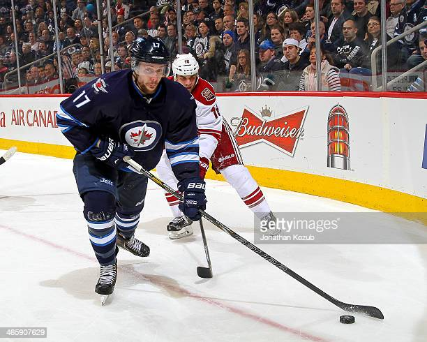 James Wright of the Winnipeg Jets plays the puck as Rostislav Klesla of the Phoenix Coyotes gives chase from behind during third period action at the...