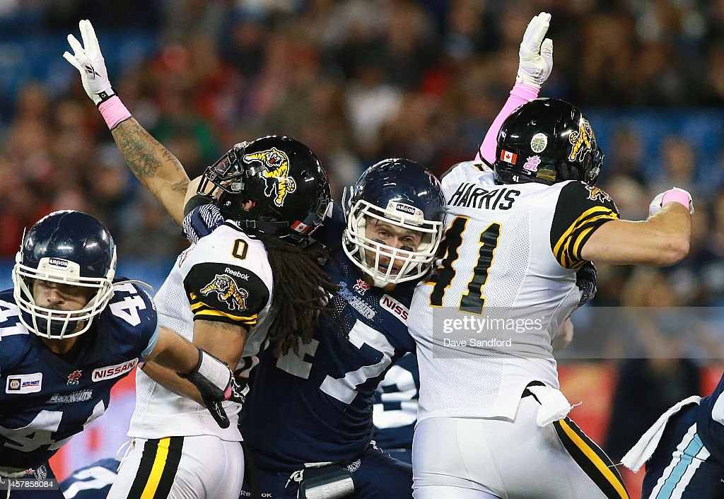 James Yurichuk of the Toronto Argonauts puts a block on both Rico Murray and Erik Harris of the Hamilton TigerCats during their game at Rogers Centre...