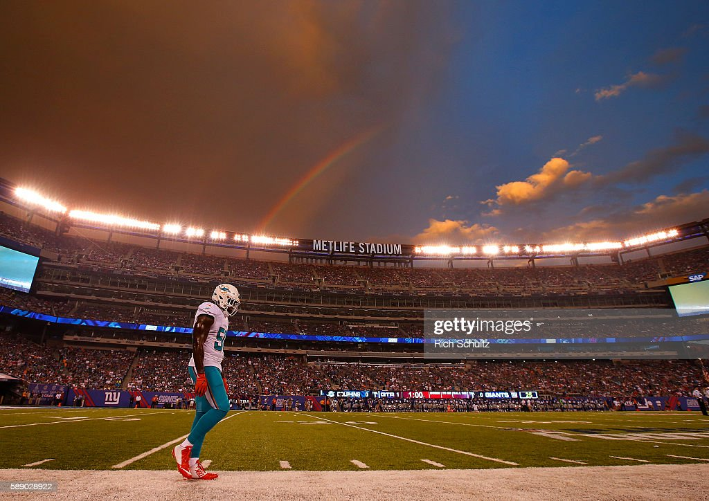 JamesMichael Johnson of the Miami Dolphins walks down the sideline as a rainbow appears over head before an NFL preseason game against the New York...