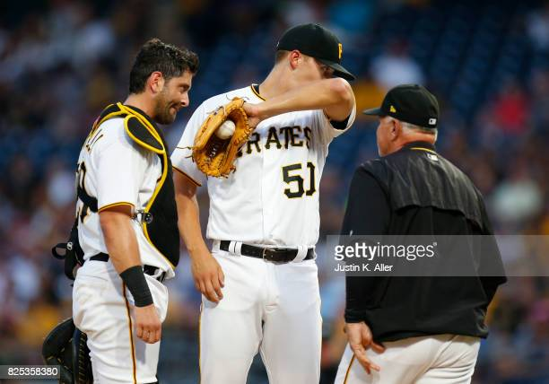 Jameson Taillon Francisco Cervelli and Ray Searage of the Pittsburgh Pirates talk during a mound visit in the third inning against the Cincinnati...