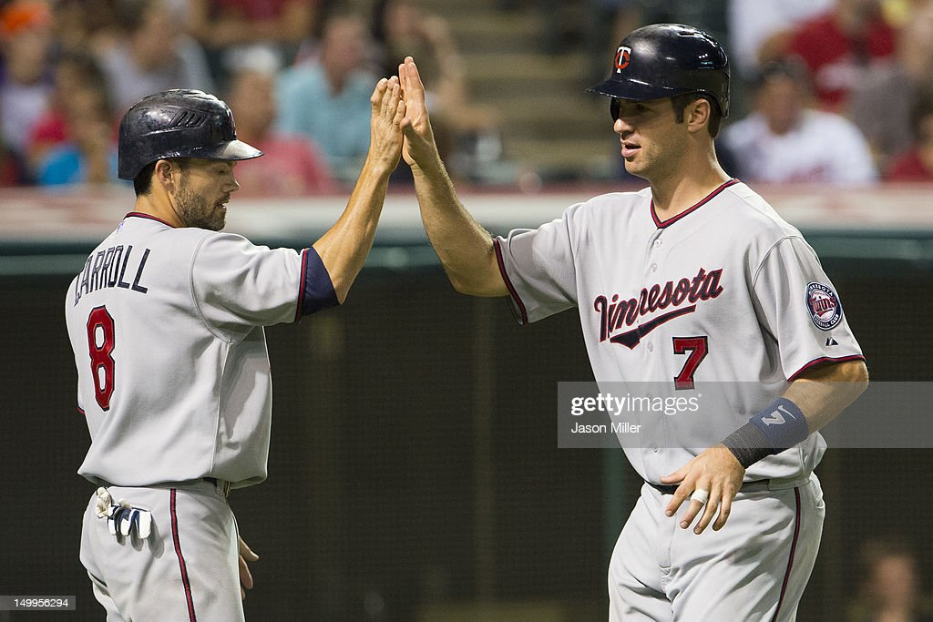 Jamey Carroll #8 and Joe Mauer #7 of the Minnesota Twins celebrate after scoring on an error during the seventh inning against the Cleveland Indians at Progressive Field on August 7, 2012 in Cleveland, Ohio.