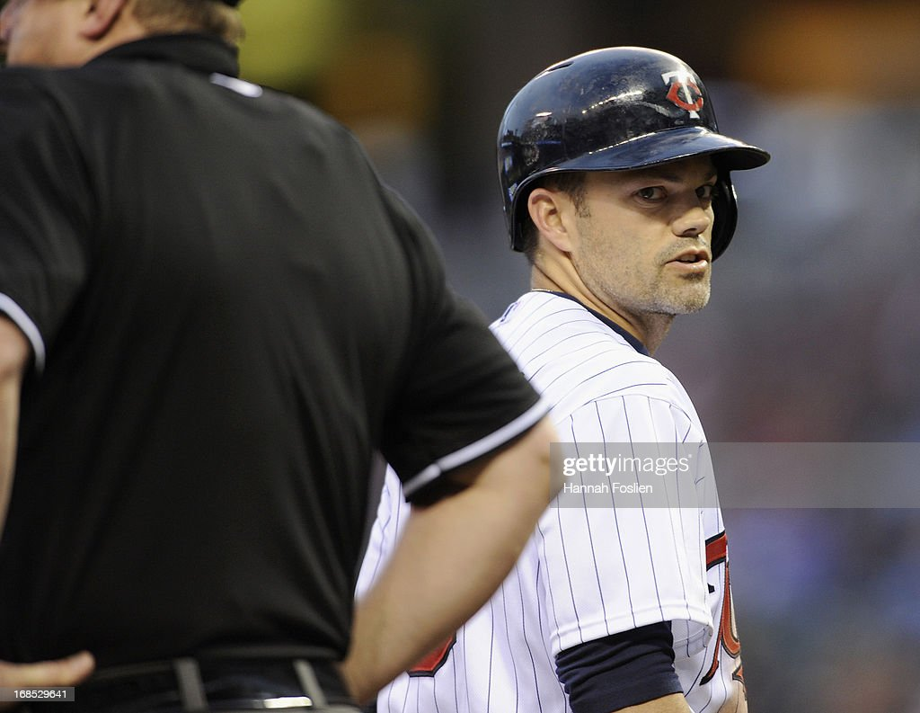 Jamey Carroll #8 of the Minnesota Twins speaks with home plate umpire Bruce Dreckman #1 after being called out on strikes during the second inning of the game against the Baltimore Orioles on May 10, 2013 at Target Field in Minneapolis, Minnesota.