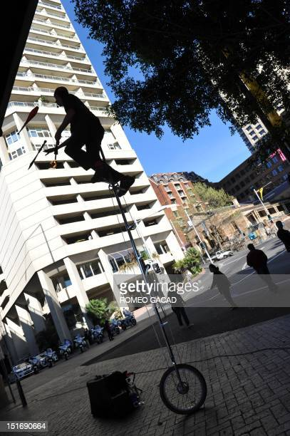 Jamey Mossengren a champion unicyclist from the US juggles while riding a 12foot tall unicycle during a street performance before an audience at...