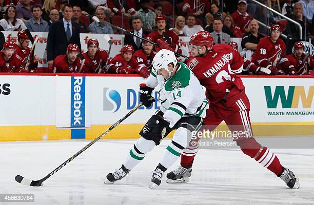 Jamie Benn of the Dallas Stars breaks in with the puck ahead of Oliver EkmanLarsson of the Arizona Coyotes during the third period of the NHL game at...