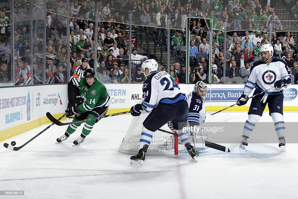<a gi-track='captionPersonalityLinkClicked' href=/galleries/search?phrase=Jamie+Benn&family=editorial&specificpeople=4595070 ng-click='$event.stopPropagation()'>Jamie Benn</a> #14 of the Dallas Stars handles the puck behind the net against <a gi-track='captionPersonalityLinkClicked' href=/galleries/search?phrase=Grant+Clitsome&family=editorial&specificpeople=4596638 ng-click='$event.stopPropagation()'>Grant Clitsome</a> #24 of the Winnipeg Jets at the American Airlines Center on October 26, 2013 in Dallas, Texas.
