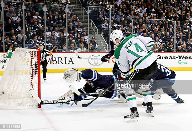 Jamie Benn of the Dallas Stars shoots the puck under a sprawling Ondrej Pavelec of the Winnipeg Jets for a third period goal at the MTS Centre on...