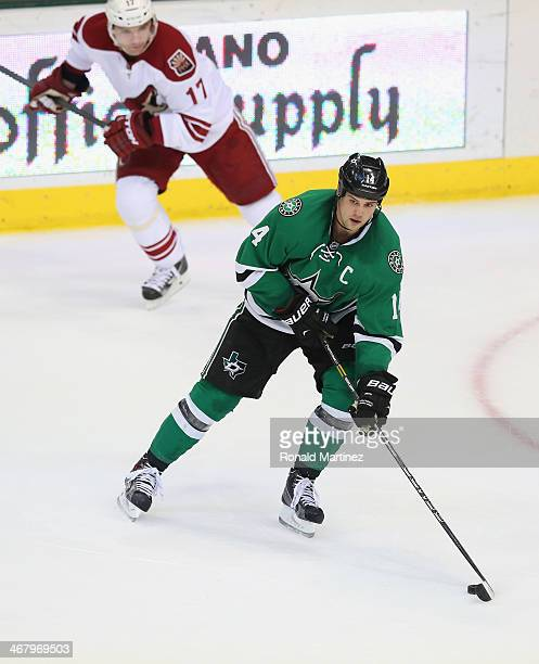 Jamie Benn of the Dallas Stars skates the puck past Radim Vrbata of the Phoenix Coyotes at American Airlines Center on February 8 2014 in Dallas Texas