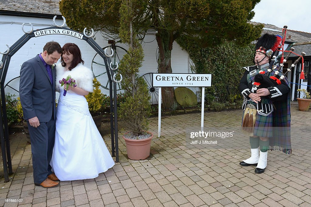 Jamie Blood and Bridget Foster pose on their wedding day at the Gretna Green Famous Blacksmiths Shop as a piper plays the bagpipes on Valentine's day on February 14, 2013 in Gretna, Scotland. Gretna Green is one of the most popular wedding destinations in Scotland hosting thousands of weddings each year with a particular rise on St Valentine's Day. Gretna Green has been hosting marriages in the blacksmiths shop since 1754.